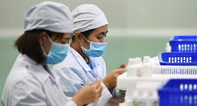 Workers manufacture hand sanitizer at a factory in Hanoi on February 14, 2020 amid concerns of the COVID-19 coronavirus outbreak. Nhac NGUYEN / AFP
